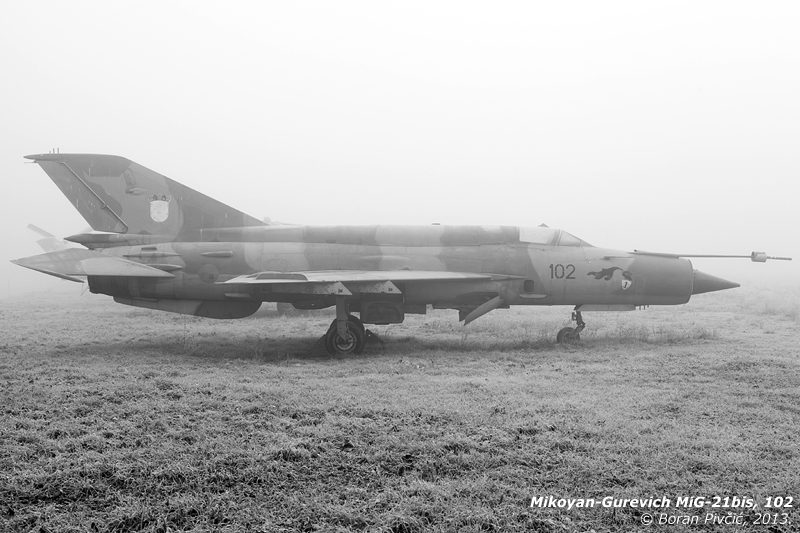 "Sad and forlorn - but still not forgotten - old 102 defies the fog on a bitterly cold morning at Zagreb, Croatia's Pleso Air Base. Named ""Osvetnik Dubrovnika"" (""Avenger of Dubrovnik""), 102 is actually a distinguished combat veteran, having defected - along with three other examples - from the Yugoslav Air Force at the start of the 90s civil war. Comprising three bis interceptors and a lone recce R model, these four would eventually become the stuff of local legend, with several of them going on to form the first proper fighter wing fielded by the nascent Croatian Air Force."