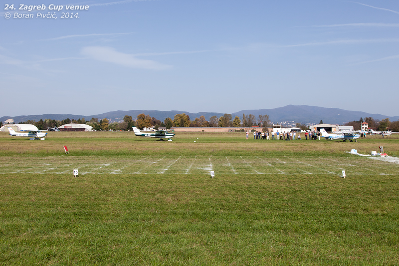"""A handy visual guide to everything you need to know about the competition. Closest to me is the landing field used for the purpose, drawn up in lime powder on the right side of RWY 28L. 72 meters long in total, it is marked off in several 5 meter wide grids, plus a two meter wide """"zero mark"""" that represents the ideal touchdown point. For 20 meters on either side, the grids are further split into one meter wide segments - as shown here - to aid the judges in determining the exact point of contact. Further back behind the field are three of the seven competition aircraft - parked on RWY 28R - with the competitors monitoring progress on the runway's edge."""