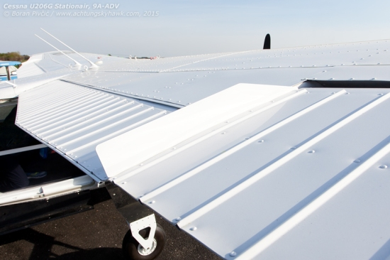 Also frequently seen on seaplanes, wing fences prevent the horizontal spill of air across the span of the wing, making the airfoil far more efficient. Interestingly, ADV's seem modified, since on all 206 floatplanes that I've seen they extend forward across the wing for at least half its chord...